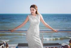 Een schitterende modelvrouw in een witte kleding met patronen op een achtergrond van het overzees De dame met donker haar is op d stock foto's