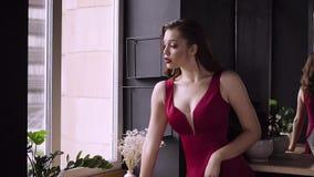 Een schitterende, roodharige dame kijkt uit het venster stock videobeelden