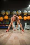 Een schitterende vrouw met perfect lichaam die het uitrekken op een gymnastiekachtergrond doen zich Aëroob, geschiktheid en bodyb royalty-vrije stock afbeelding