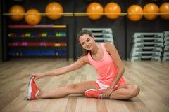 Een schitterende vrouw met perfect lichaam die het uitrekken op een gymnastiekachtergrond doen zich Aëroob, geschiktheid en bodyb royalty-vrije stock fotografie