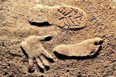 Een schoendruk, een voetafdruk en een palmdruk op bruin zand stock afbeelding