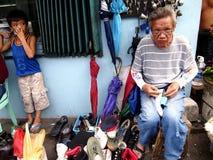 Een schoenmaker herstelt een schoen voor een klant langs een straat in Antipolo-Stad, Filippijnen Stock Fotografie