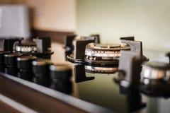 Een schone en glanzende kooktoestelhaardplaat en knoppen Binnen genomen met gouden licht die op het toestel glanzen stock foto
