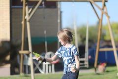 Een school-age jongensspelen met een waterpistool stock fotografie
