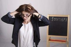 Een schoolleraar met een chagrijnig blik chagrijnig blik, die zijn hoofd houden royalty-vrije stock foto
