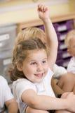 Een schoolmeisje heft haar op indient een primaire klasse Stock Foto's