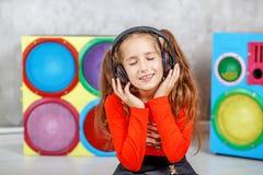 Een schoolmeisje luistert aan muziek in de hoofdtelefoons Concept mu Royalty-vrije Stock Foto's