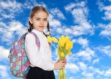 Een schoolmeisje met een boeket van bloemen en een rugzak op haar sho stock foto's