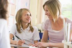 Een schoolmeisjezitting met haar leraar in klasse Stock Foto