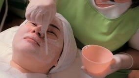 Een schoonheidsspecialist in handschoenen maakt een vrouwelijk gezicht met hulpmiddelen schoon De procedure van verjonging en het stock videobeelden