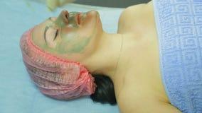 Een schoonheidsspecialist in handschoenen verwijdert een kleimasker uit een vrouwens gezicht met een katoenen stootkussen Zachte  stock videobeelden