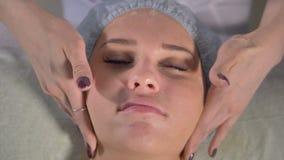 Een schoonheidsspecialist verstrekt een handgezichtsmassage stock video