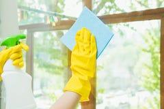 Een schoonmakend bedrijf maakt het venster van vuil schoon De huisvrouw poetst de vensters van het huis op stock afbeelding