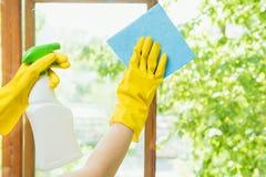 Een schoonmakend bedrijf maakt het venster van vuil schoon De huisvrouw poetst de vensters van het huis op royalty-vrije stock foto's