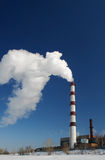 Een schoorsteen die net in de blauwe hemel rookt Stock Foto