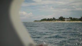 Een schot van het dek van snel varende boot die zich van mooi eiland bewegen stock footage