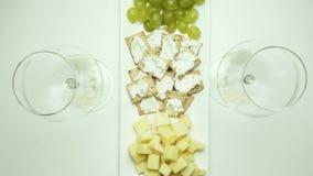 Een schotel met een snack wordt gezet op de lijst, twee glazen voor wijn en gegoten Hoogste mening stock footage