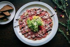 Een schotel van vlees en groenten op een witte plaat Stock Foto