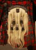 Een Schots tasje op een oude kilt Stock Foto's