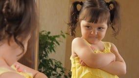 Een schuw meisje kijkt in de spiegel Mooi meisje in een gele kleding bij een spiegel Een kind met staarten op zijn hoofd stock footage