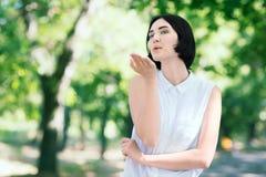 Een schuw, vrolijk en jong wijfje met positieve emoties in het park De schitterende dame met het gebaar van de luchtkus E Royalty-vrije Stock Foto