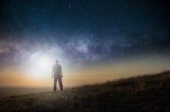 Een science fictionconcept Een mens die zich op een heuvel bevinden die uit over ruimte met een helder licht in de hemel kijken royalty-vrije stock foto