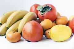 Een selectie van geschikte verschillende verse vruchten van bananen, mandarins, dadelpruimen en citroenen op witte achtergrond di stock afbeelding