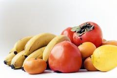 Een selectie van geschikte verschillende verse vruchten van bananen, mandarins, dadelpruimen en citroenen op witte achtergrond di stock foto's