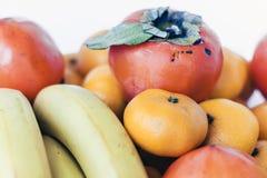 Een selectie van geschikte verschillende verse vruchten van bananen, mandarins, dadelpruimen en citroenen op witte achtergrond di stock afbeeldingen