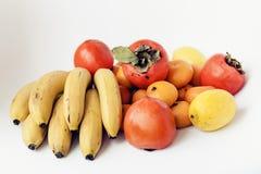 Een selectie van geschikte verschillende verse vruchten van bananen, mandarins, dadelpruimen en citroenen op witte achtergrond di royalty-vrije stock afbeelding