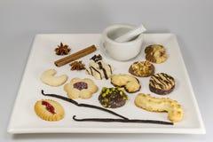 Een selectie van theeingrediënten, koekjes en een mortier en een stamper stock foto