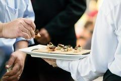 Een server die een dienbladhoogtepunt van snacks houden tijdens een gerichte gebeurtenis royalty-vrije stock afbeeldingen