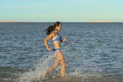 Een sexy jong donkerbruin vrouw of een meisje die een bikini dragen die de branding op een verlaten tropisch strand met een blauw royalty-vrije stock afbeeldingen