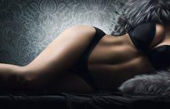 Een sexy vrouw die in erotische lingerie en bont legt Stock Foto's