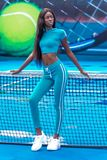 Een sexy zwart vrouwelijk model met een tennisracket stock foto