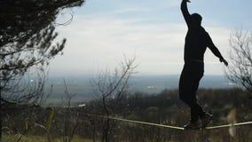 Een silhouet die van de mens een hoed en een baard dragen loopt slackline tijdens de wind tegen de achtergrond van de Kaukasus stock videobeelden