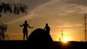 Een silhouet die van een paar, om een tent lopen Een jonge man probeert de achterstand in te lopen een jonge vrouw stock footage
