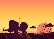 Een silhouet van een jongen die een meisjes` s wang kussen tijdens zonsondergang Stock Foto