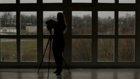 Een silhouet van een meisjesfotograaf tegen het venster stock footage