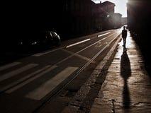 Een silhouet van een persoon in de straat met lange schaduw Stock Foto