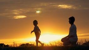 Een silhouet van een gelukkig jong jongenskind die de wapens van zijn houdende van moeder voor een omhelzing, voor de zonsonderga stock videobeelden