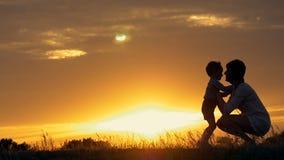 Een silhouet van een gelukkig jong jongenskind die de wapens van zijn houdende van moeder voor een omhelzing, voor de zonsonderga stock video
