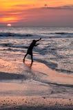 Een silhouet van een mens die een werpnet voor aasvissen werpen met stock foto's