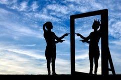 Een silhouet van een narcistische vrouw heft haar zelfrespect voor een spiegel op stock fotografie