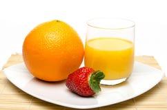 Een sinaasappel, een aardbei en een jus d'orange Stock Afbeelding