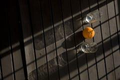Een sinaasappel en twee glazen in de ochtend stellen in Puncak Bogor in de schaduw Stock Afbeeldingen