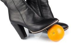 Een sinaasappel onder de zwarte laarzen van de leerdame stock foto