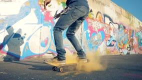 Een skateboarder berijdt, langzame motie Mensensprongen op een vleet met gele kleur op het stock footage