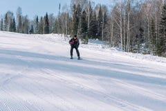 Een skiër berijdt van een hoge berg Het van brandstof voorzien van de benzinepomp Actieve levensstijl gezondheid stock afbeelding