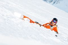 Een skiër in oranje algemeen en met een rugzak ligt gelukkig in de sneeuw na het vallen Royalty-vrije Stock Foto's